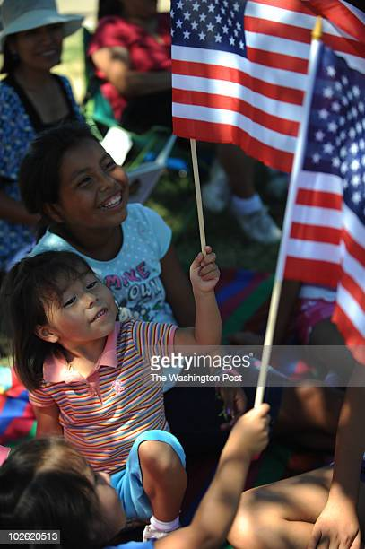 Gabriella Quito Isabella Quito and Shirley Quito wave American flags as they wait for The National Independence Day Parade on Sunday, July 4, 2010....