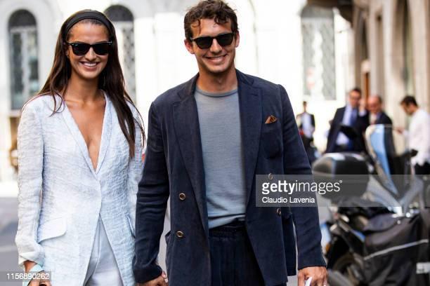 Gabrielle Caunesil , wearing a light grey blazer, light grey silky trousers and light blue Giorgio Armani bag, and Riccardo Pozzoli , wearing a dark...