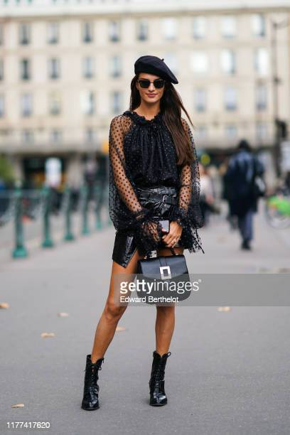 Gabrielle Caunesil wears a black beret, sunglasses, a frilly collar, a black mesh lace top with printed polka dots, a balck leather skirt with belts,...