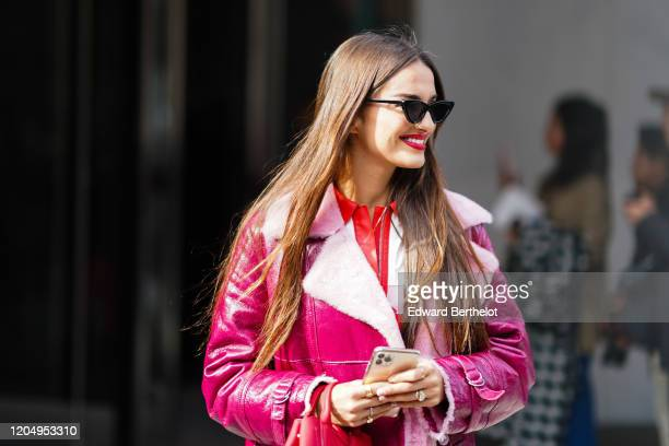 Gabrielle Caunesil wears sunglasses, a pink leather aviator long jacket with wool inner lining, outside Longchamp, during New York Fashion Week...