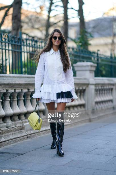 Gabrielle Caunesil wears sunglasses, a white long ruffled shirt/dress, a yellow quilted bag, black shiny tigh high boots, outside Viktor & Rolf,...
