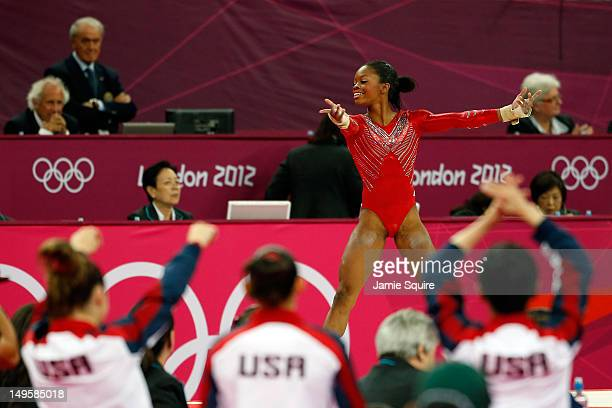 Gabrielle Douglas of the United States performs on the floor exercise as her team cheers her on in the Artistic Gymnastics Women's Team final on Day...