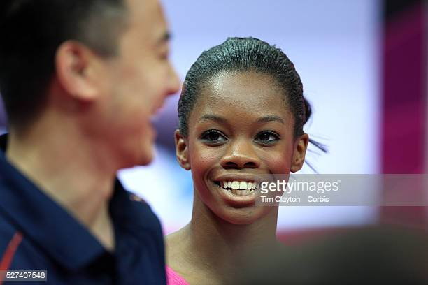 Gabrielle Douglas USA shares a joke with the USA coaches during the Women's Artistic Gymnastics podium training at North Greenwich Arena during the...