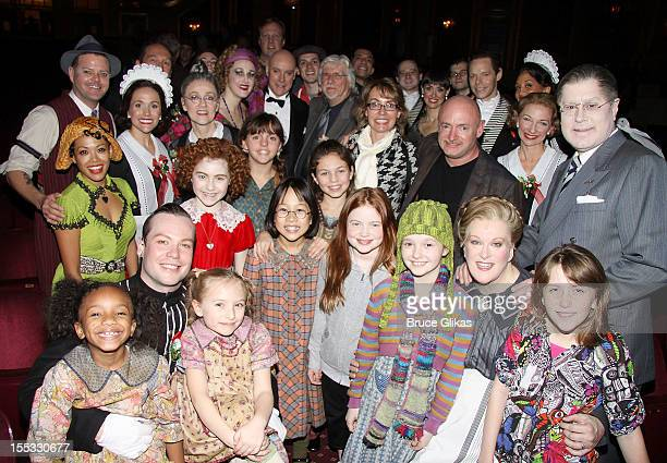 Gabrielle Giffords and husband Mark E Kelly pose with the cast backstage at the hit revival of 'Annie' on Broadway at The Palace Theater on November...