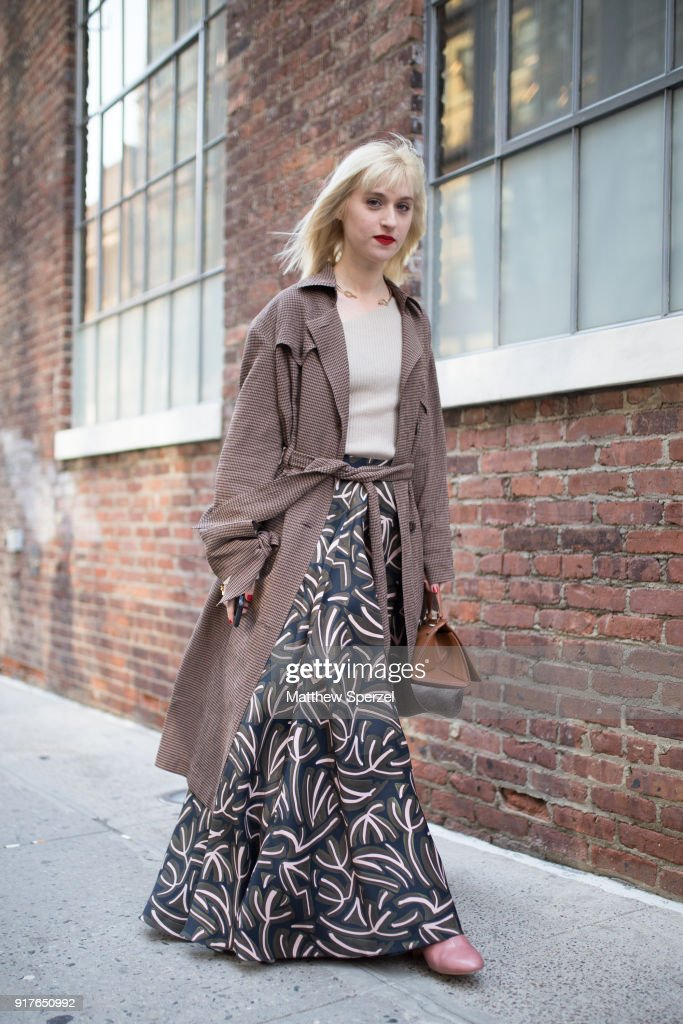 Gabrielle Korn is seen on the street attending Zadig & Voltaire during New York Fashion Week wearing a brown coat with black pattern skirt and beige top on February 12, 2018 in New York City.