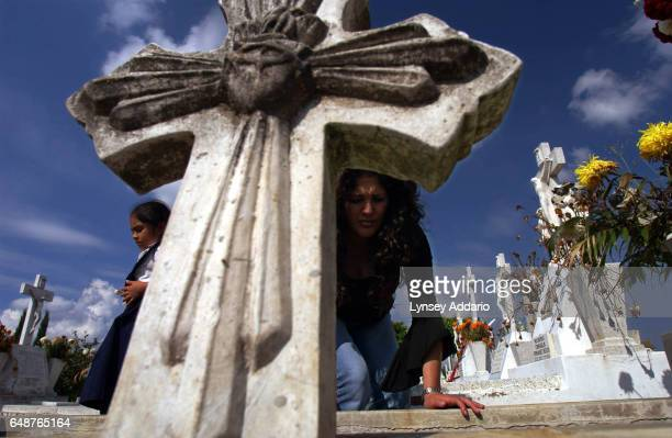 Gabrielle Ortega Blanco stands with her daughter over the unfinished grave of her mother in a cemetery in Guadalajara Mexico Nov 9 2002 Though the...