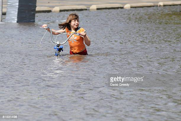 Gabrielle Steenblock walks across a flooded street near downtown June 11, 2008 in Cedar Rapids, Iowa. Several areas of the city have already been...