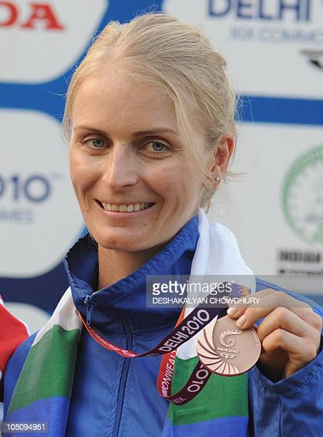Gaby Ahrens of Namibia poses with the bronze medal during the women's singles trap shooting medal ceremony at the Dr Karni Singh Shooting Range of...