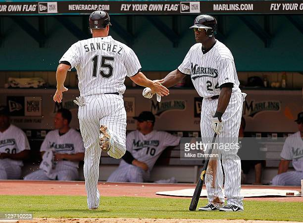 Gaby Sanchez of the Florida Marlins is congratulated by Mike Cameron after scoring during a game against the Philadelphia Phillies at Sun Life...