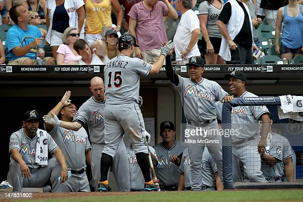 Gaby Sanchez of the Miami Marlins clebrates outside the dugout after hitting a solo home run off of Brewers closer John Axford in the top of the 9th...