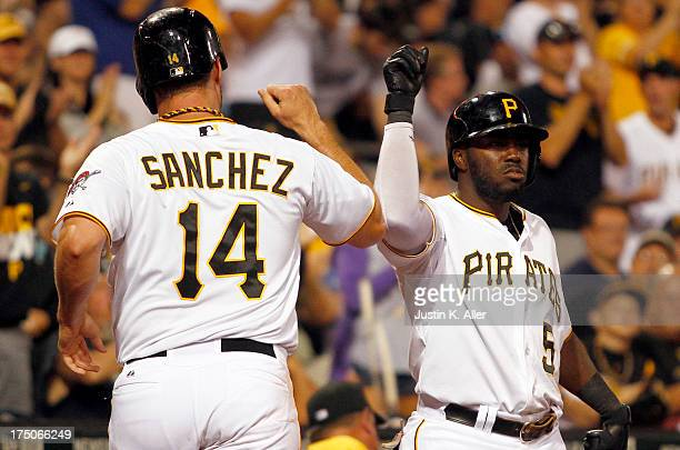 Gaby Sanchez of the Pittsburgh Pirates celebrates with Josh Harrison after scoring on a seventh inning sacrifice fly against the St Louis Cardinals...