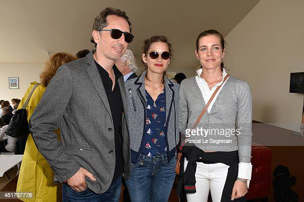 Gad Elmaleh Marion Cotillard and Charlotte Casiraghi attend the Paris Eiffel Jumping presented by Gucci at ChampdeMars on July 5 2014 in Paris France