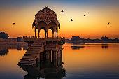 Gadisar lake at Jaisalmer Rajasthan at sunrise with ancient temples and archaeological ruins.