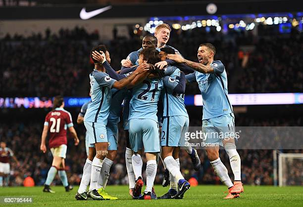 Gael Clichy of Manchester City is mobbed by team mates after scoring the opening goal during the Premier League match between Manchester City and...