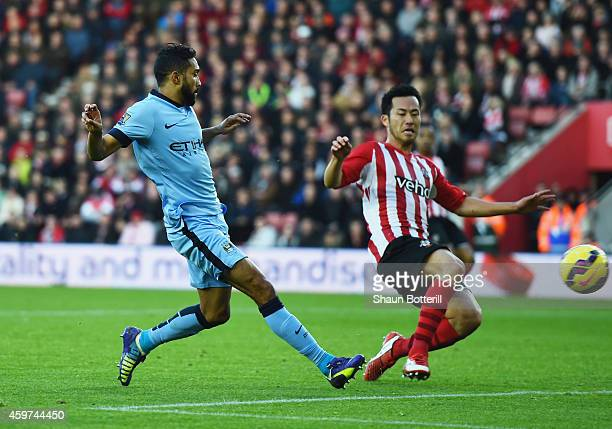 Gael Clichy of Manchester City shoots past Maya Yoshida of Southampton to score their third goal during the Barclays Premier League match between...