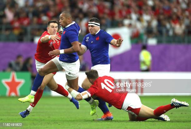 Gael Fickou of France breaks the tackle of Owen Watkin and Dan Biggar of Wales during the Rugby World Cup 2019 Quarter Final match between Wales and...
