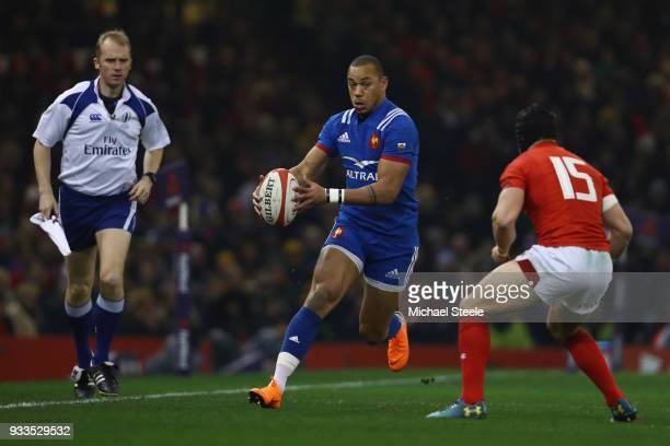 Gael Fickou of France runs at Leigh Halfpenny of Wales as assistant referee Wayne Barnes looks on during the NatWest Six Nations match between Wales...