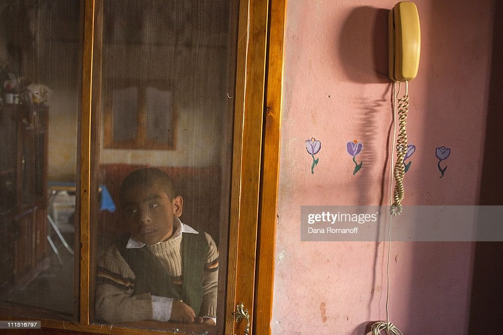 Gael Hernandez Tejeda, six, stands in the doorway to his kitchen on November 23, 2009 in San Pablo Huixtepec. Gael only knows his father and older brother that live as undocumented immigrants in the United States through weekly telephone calls and photographs. Children like Gael grow up not knowing their fathers and dream of their future in the US.