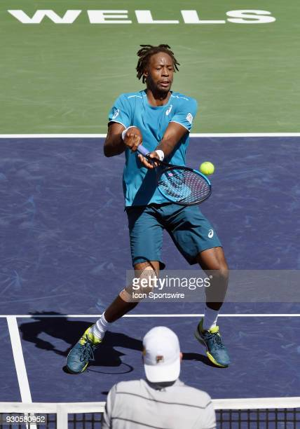 Gael Monfils exchanges shots at the net with John Isner during the first set of a match played during the BNP Paribas Open played on March 11 2018 at...