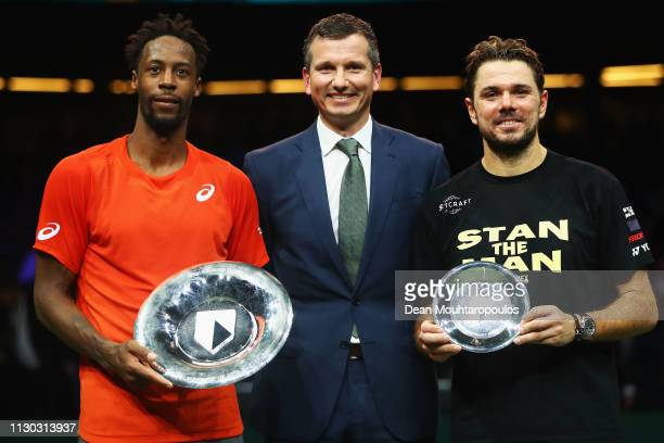 Gael Monfils of France celebrates his victory against Stan Wawrinka of Switzerland as they pose with their trophies and Richard Krajicek after the...