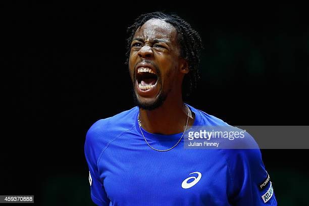 Gael Monfils of France celebrates winning a game against Roger Federer of Switzerland during day one of the Davis Cup Tennis Final between France and...