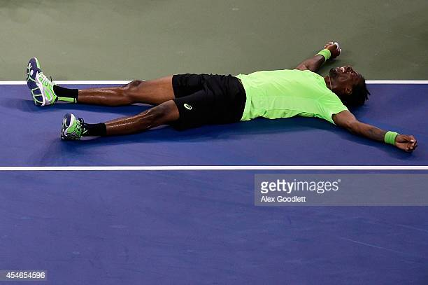 Gael Monfils of France falls on the court against Roger Federer of Switzerland during their men's singles quarterfinal match on Day Eleven of the...