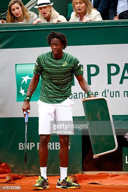 Gael Monfils of France holds a line judge stand after falling into it during his Men's Singles match against Pablo Cuevas of Uruguay on day six of...