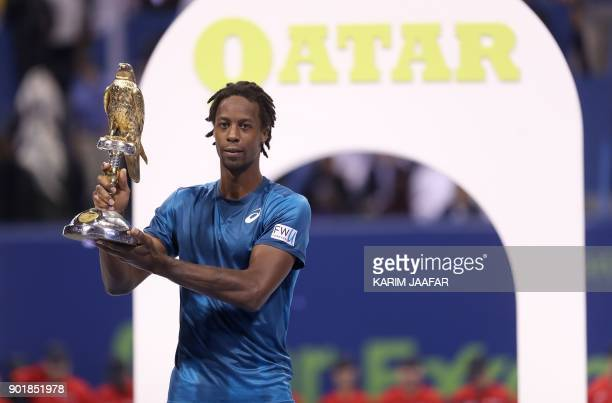 TOPSHOT Gael Monfils of France holds the winner's trophy after winning against Russia's Andrey Rublev in the ATP Qatar Open tennis competition in...