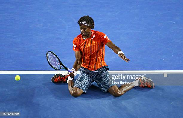 Gael Monfils of France plays a forehand on his knees in his quarter final match against Milos Raonic of Canada during day 10 of the 2016 Australian...