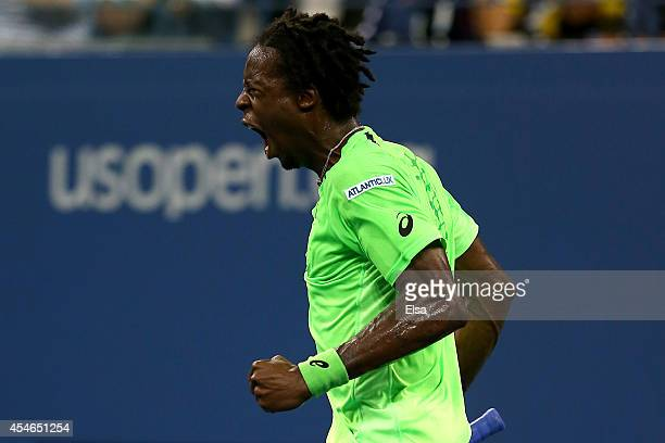 Gael Monfils of France reacts to a point against Roger Federer of Switzerland during their men's singles quarterfinal match on Day Eleven of the 2014...