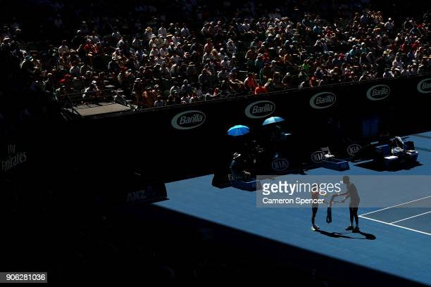 Gael Monfils of France receives a towel from a ball kid in his second round match against Novak Djokovic of Serbia on day four of the 2018 Australian...