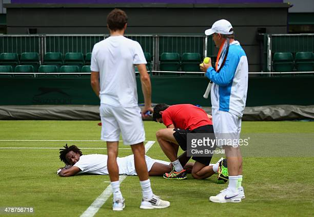 Gael Monfils of France receives treatment after slipping over during a practice session prior to the Wimbledon Lawn Tennis Championships at the All...