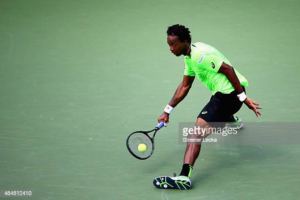 Gael Monfils of France returns a shot to Grigor Dimitrov of Bulgaria during their men's singles fourth round match on Day Nine of the 2014 US Open at...