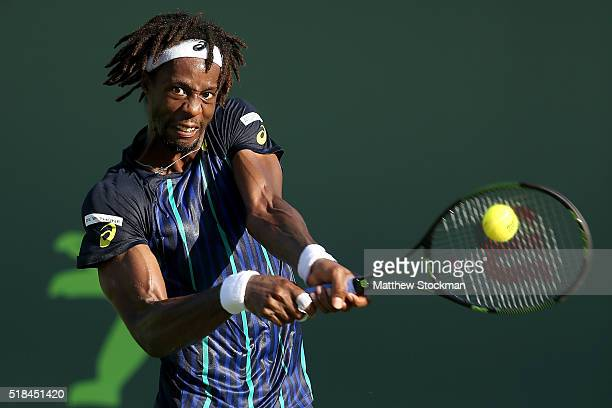 Gael Monfils of France returns a shot to Kei Nishikori of Japan during the Miami Open presented by Itau at Crandon Park Tennis Center on March 31...
