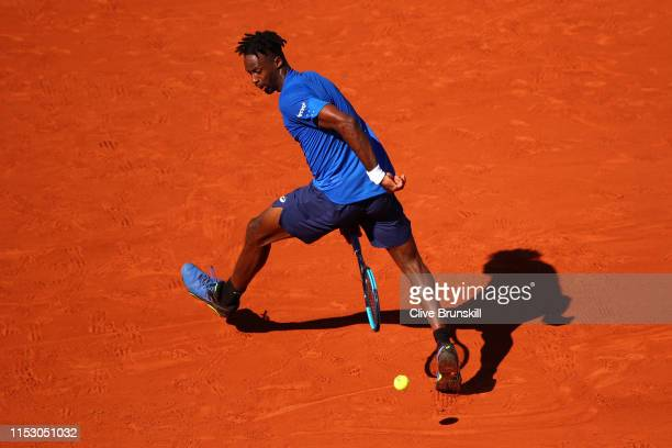 Gael Monfils of France returns the ball through his legs during his mens singles third round match against Antoine Hoang of France during Day seven...