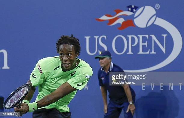 Gael Monfils of France returns the ball to Roger Federer of Switzerland during their men's singles quarterfinal tennis match on Day 11 of the 2014 US...