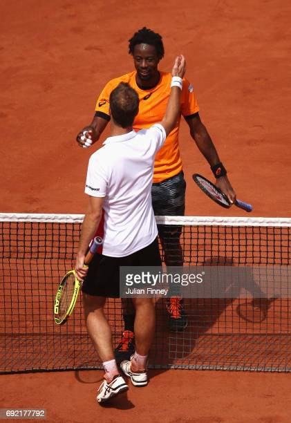 Gael Monfils of France smiles at the net with Richard Gasquet of France after Gasquet retired in their men's singles third round match during day...
