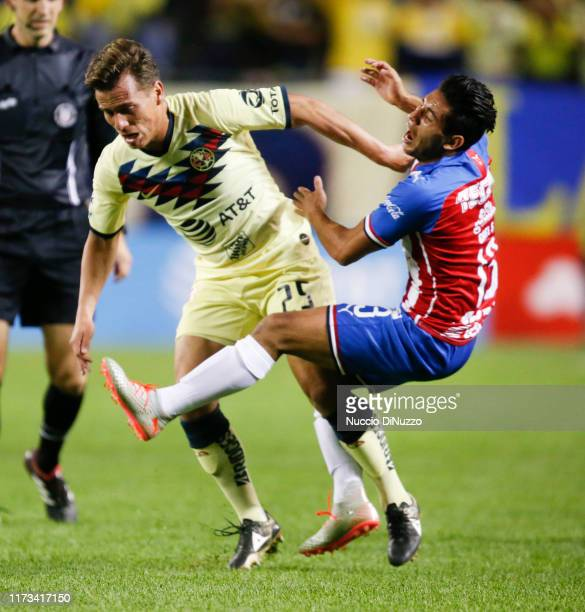 Gael Sandoval of Chivas de Guadalajara is fouled by Fernando Gonzalez of Club America during the Super Clasico game at Soldier Field on September 08...
