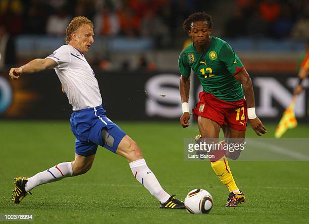 Gaetan Bong of Cameroon evades the tackle by Dirk Kuyt of the Netherlands during the 2010 FIFA World Cup South Africa Group E match between Cameroon...