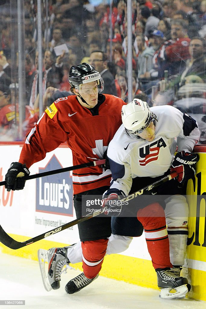 Gaetan Haas #11 of Team Switzerland body checks Charlie Coyle #3 of Team USA during the 2012 World Junior Hockey Championship Relegation game at the Scotiabank Saddledome on January 4, 2012 in Calgary, Alberta, Canada.