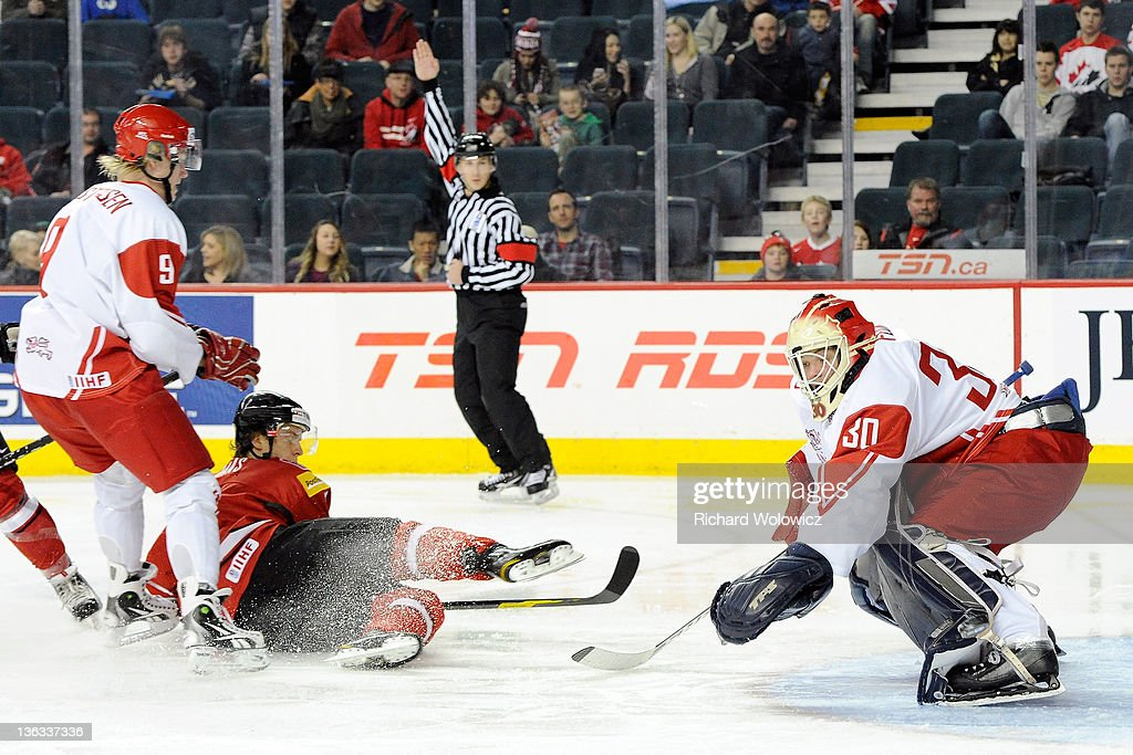 Gaetan Haas #11 of Team Switzerland is taken down on a breakaway by Emil Kristensen #9 of Team Denmark during a relegation game at the 2012 World Junior Hockey Championships at the Saddledome on January 2, 2012 in Calgary, Alberta, Canada.