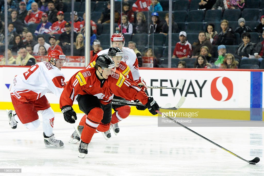 Gaetan Haas #11 of Team Switzerland stick handles the puck on a breakaway while being chased by Emil Kristensen #9 of Team Denmark during a relegation game at the 2012 World Junior Hockey Championships at the Saddledome on January 2, 2012 in Calgary, Alberta, Canada.