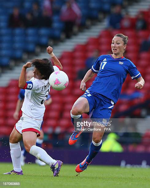 Gaetane Thiney of France challenges Myong Gum Kim of Korea DPR during the Women's Football first round Group G Match of the London 2012 Olympic Games...