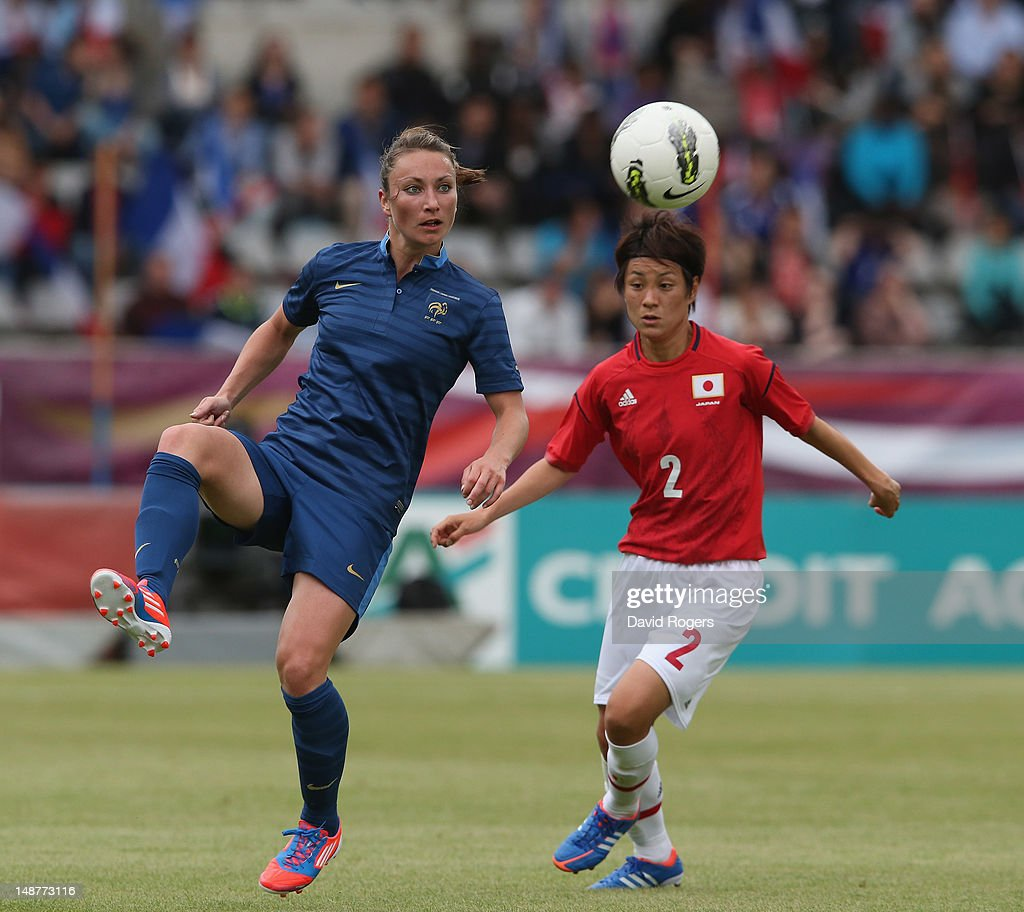 Gaetane Thiney of France clears the ball watched by Yukari Kinga during the friendly international match between Japan Women and France Women at Stade Charlety on July 19, 2012 in Paris, France.