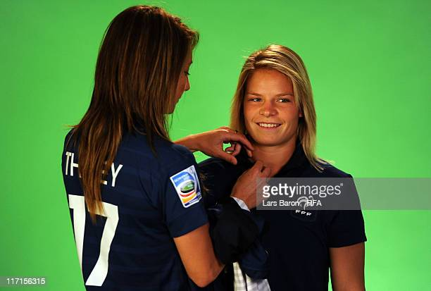 Gaetane Thiney of France helps team mate Eugenie le Sommer during the FIFA portrait session on June 23 2011 in Heidelberg Germany