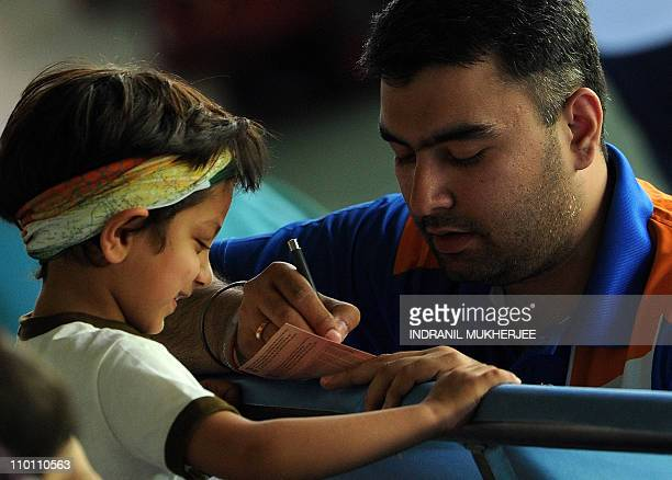 Gagan Narang of India signs his autograph for a young fan after the men's pair 50 m rifle prone event during the XIX Commonwealth Games at the Karni...