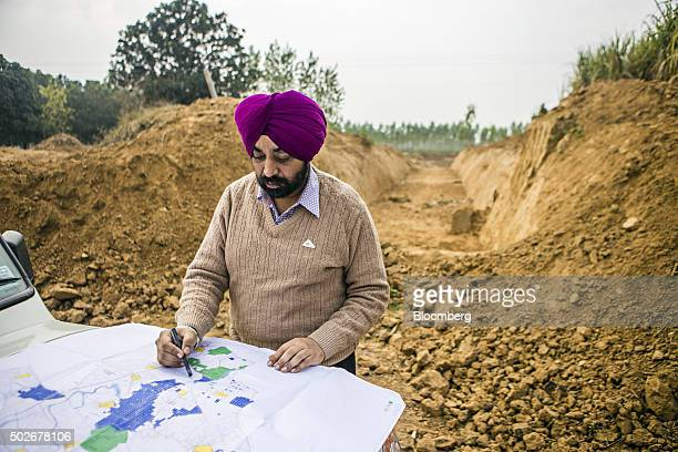 Gagandeep Singh a development officer for Yamuna Nagar district stands with a map at the site of a newlydug canal along the purported ancient route...