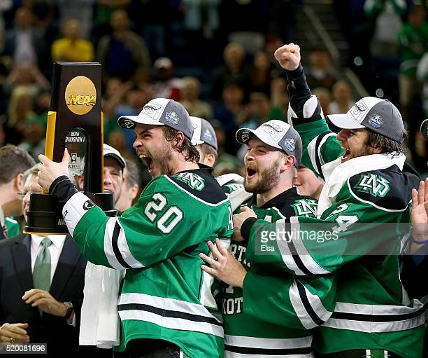 Gage Ausmus of the North Dakota Fighting Hawks celebrates with the championship trophy with teammates Colten St Clair and Christian Wolanin after the...