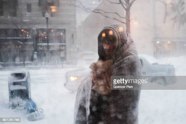 Gage who is homeless pauses outside of a coffee shop on the streets of Boston as snow falls from a massive winter storm on January 4 2018 in Boston...