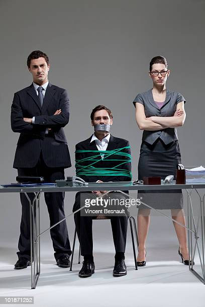 Gagged and bondaged businessman with two employees